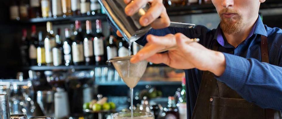 barman-with-shaker-preparing-cocktail-at-bar-P57KVCX